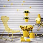 Gartenstuhl, Gießkanne und Blumentöpfe in Gelb